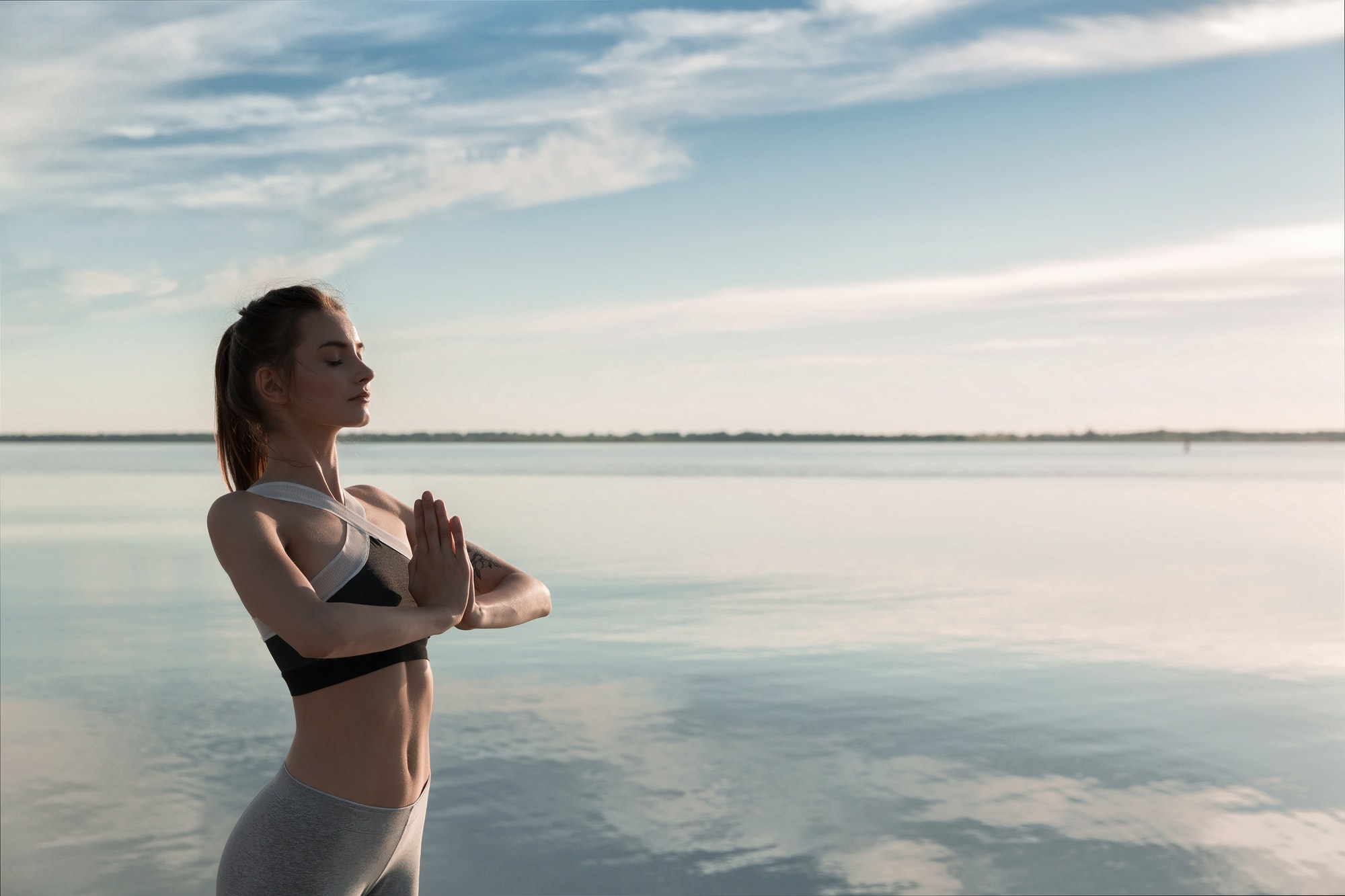 Sports beautiful woman at the beach meditation.